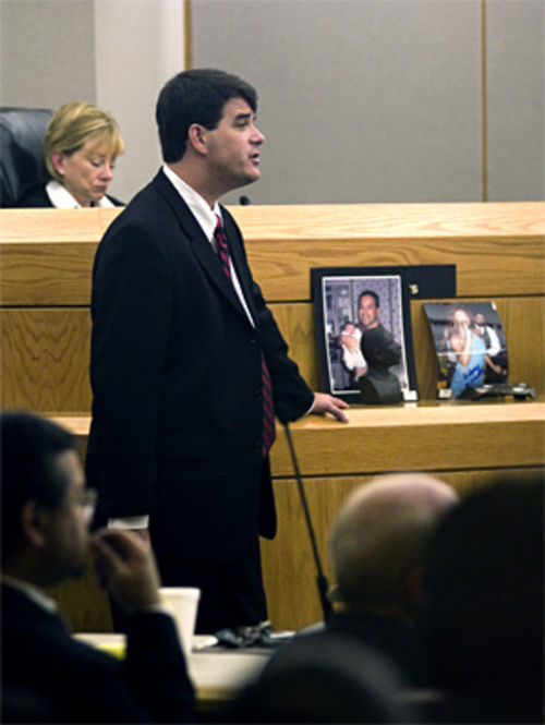 "Prosecutor Fred Burns in court next to photos of Oscar holding his baby and suspect Edgar ""Richie"" Acevedo in drag"