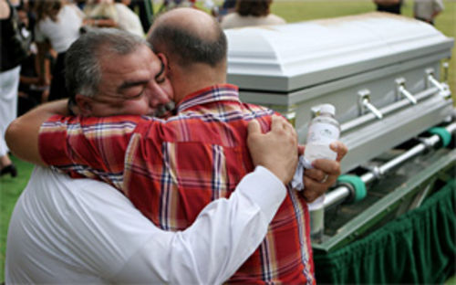 Roy Velez hugs a friend after his son Andrew's funeral at Lubbock's Resthaven Memorial Park on August 4, 2006.
