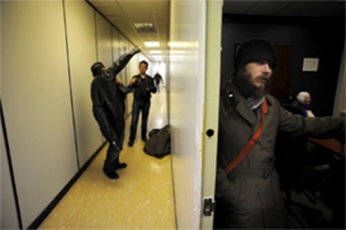 Deserter Ryan Johnson (right) readies himself for the cold after a weekly meeting at the War Resisters Support Campaign headquarters in Toronto.