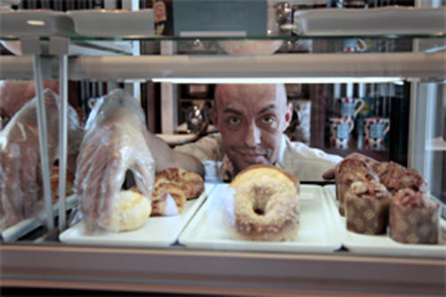 Stephen Barley, a barista recovering from a five-and-a-half-year stint at Starbucks, sets out the morning's baked offerings at It's a Grind.