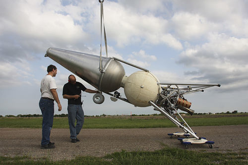 Eaton (left) and Mike Vinther prepare the rocket for a test flight at Armadillo's Caddo Mills Airport headquarters.
