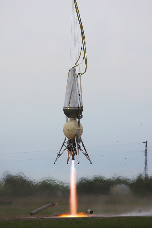 A rocket lifts up on a short test flight, powered by liquid oxygen and ethanol, and tied to a crane above.
