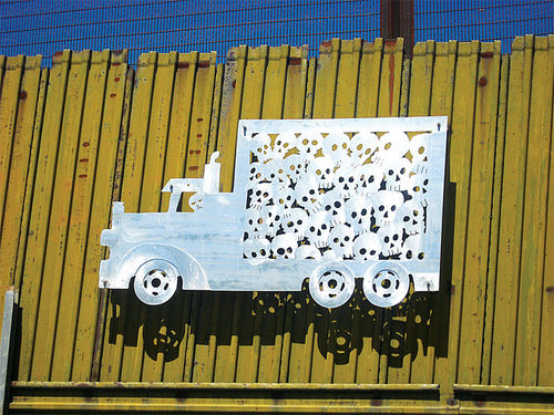 In this artwork, on the border fence in Nogales, Sonora, the skulls stuffed in the back of a truck illustrate violence immigrants experience at the hands of Border Patrol agents. Also, that many immigrants do not survive their journey.