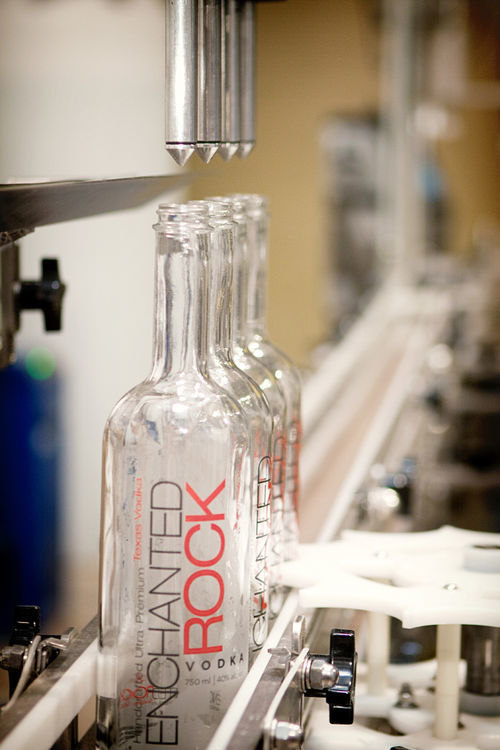 Bottles line up for filling with Rebecca Creek Distillery's Enchanted Rock Vodka. The San Antonio distillery sells candles, shirts and vodka, which is much quicker to bring to market, while it waits for its bourbon to age.