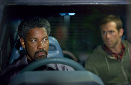 Denzel Washington and Ryan Reynolds in a scene from Safe House in which Reynolds, unfortunately, is wearing a shirt.