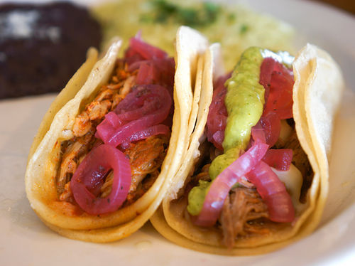 Cafe Maya steps away from traditional Tex-Mex with cochinita (left) and barbacoa tacos.