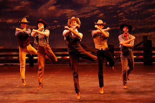 Giddyap! Hayden Clifton (center) leads the line of dancing cowpokes in Lyric Stage's high-steppin' Oklahoma!