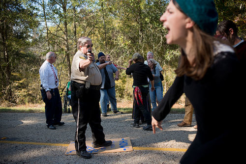 A Cherokee County Sheriff's deputy threatens to pepper-spray protesters a second time if they don't clear the road.