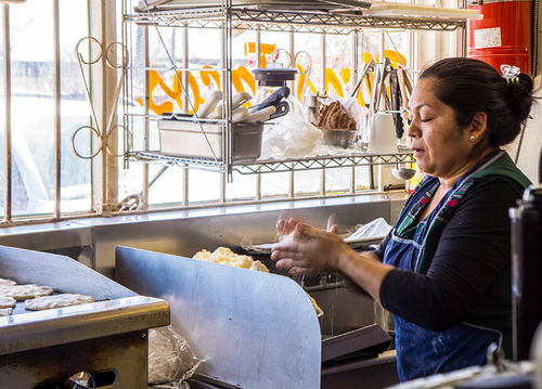 Ana Ortiz and her employees pat out hundreds of pupusas each day.