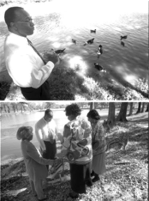 Lenell Geter prays with friends and feeds the ducks at the park in Greenville, where he first noticed a policeman copying down the license plate of his parked car. Geter was later arrested at his apartment. The park is where Geter often spent his lunch hour feeding the ducks.