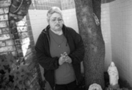 Maria Reyna stands beside the tree in her Pleasant Grove front yard where she first saw an image of Mary 19 years ago. Look to the left of the rag, and you will see a lighter area of the tree. That's where the Virgin Mary's head is, and the rest of her body is the lighter area below.