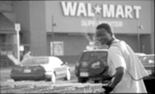 What every kid dreams of: Peter Nyarol Dut pushes carts at a Wal-Mart, which sells the American dream for cheap.