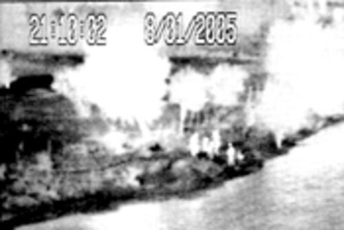 A thermal image, shows a group of people hanging out on the other side of the river.