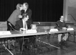 Former council member Jim Buerger looks on while Miller and Dunning kiss at a debate. Oh, yuck.