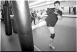Fighter-trainer Joe Garcia unloads on a heavy bag. Thai kickboxing is one of the big, flashy weapons in mixed martial arts.