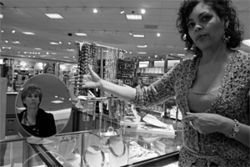Liz Tanner (in mirror) sizes up a necklace suggested by her personal shopper.