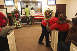 Friends and family members comfort one another during a viewing.