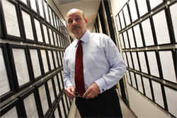 DWI lawyer David Burrows in the hallway leading to his corner office, surrounded by framed not-guilty verdicts.