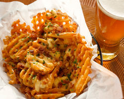 Cheese fries boast confetti of bacon and chive.