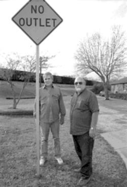 Neighbors Roger Nickel and Richard Deniker near one of the trains that rattle their neighborhood