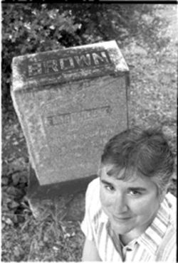 DPD Detective Shari Degan believes she has solved the 1913 murder of Florence Brown. Here Degan, current president of the Dallas Genealogy Society, poses by the Brown grave site in Oakland Cemetery.