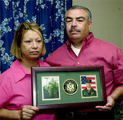 Carmen and Roy Velez show photos of the sons they lost to the War on Terror—one to the invasion of Fallujah and the other to suicide, which is on the rise in the Army.