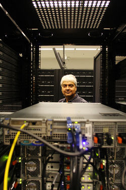 Kaushik De, a physics professor at UTA, in a room full of computer servers that processed data that helped locate the Higgs boson.