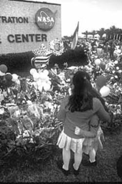 Two girls hug each other in front of the memorial at Johnson Space Center.
