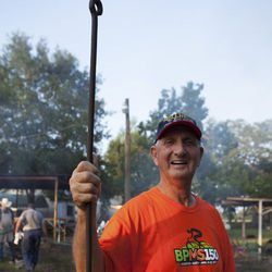 Pitmaster Herbert Schumann lifts one of the metal rods used to hold the meat before the baskets were introduced.