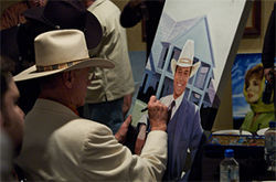 Hagman, still wearing his trademark hat, signs an image of his younger self as J.R.