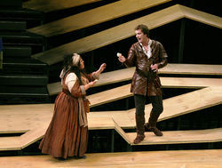 Christina Vela, as Mistress Quickly, and Steven Walters, as Prince Hal, wade across waves of plywood on designer John Coyne's set for Henry IV.