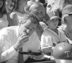 The hotdog looks good, but lose the stiff shirt. Then-Gov. George W. Bush noshes at a Texas Rangers game with current team owner Tom Hicks in 1998.