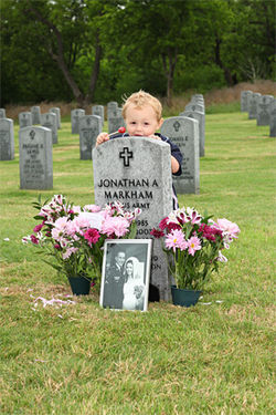 Daniel Markham, 1, kisses his father's gravestone. His mother, Stacey,  had taken him with her to DFW National Cemetery to commemorate her and her husband's third wedding anniversary.