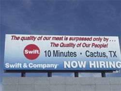 A billboard advertises jobs at the plant.