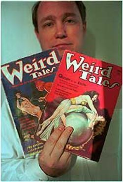 Plano collector Paul Herman with two old issues of Weird Tales, which Howard wrote for.