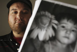 Joshua Maydon displays a photo of his young daughter, whom he claims doesn&amp;#146;t receive his child
