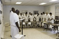 A group of inmates pray before beginning a class.