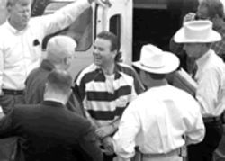Tommy Lynn Sells--center, with beatific smile--arrives in Little Rock in March. Texas Rangers brought him there to talk to local authorities about two murders he claims to have committed.