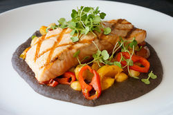 Salmon a la Parilla: Grilled salmon in a black-bean puree, garbanzo beans, heirloom tomatoes and banana-pepper salad with coriander crema.