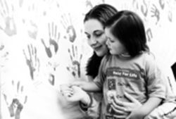 Mother and daughter put handprints on the Survivors'  Wall.