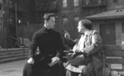 Neo (Keanu Reeves, dressed like a Jesuit) gets some advice from the Oracle (Gloria Foster).