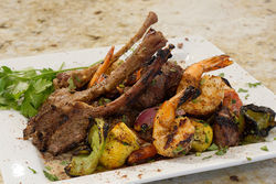 Beef, chicken, shrimp and other kebabs turn over a gas grill at Nora.
