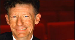 Lyle Lovett grins from ear to ear—the same ear.