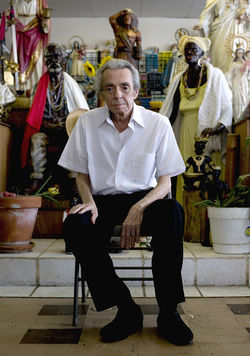 "Francisco ""Pancho"" Diaz, owner of Chango Botánica, sits in front of a statute of El Negro (left), a spirit guide whom  Diaz says convinced him to open his shop nearly 33 years ago."