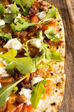 A flatbread topped with chicken and goat cheese.