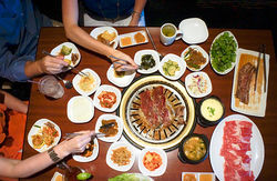 Short ribs and brisket cook on the grill, surrounded by banchan, a collection of side dishes that accompany every meal.