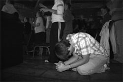 A teenager prays on his knees during a Teen Mania worship service. Passionate displays of faith are encouraged at the Honor Academy.