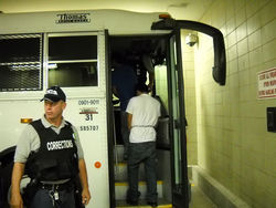 A bus for Corrections Corporation of America picks up migrants sentenced to time in custody by a Tucson magistrate.