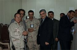 In Iraq in 2003 as a civilian translator under contract with the U.S. Air Force, Kirkuki (center) poses with Kirkuk&#039;s mayor and city council members.