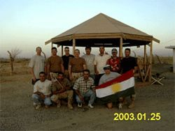 Kirkuki with a group of officers and translators holding the Kurdish flag.